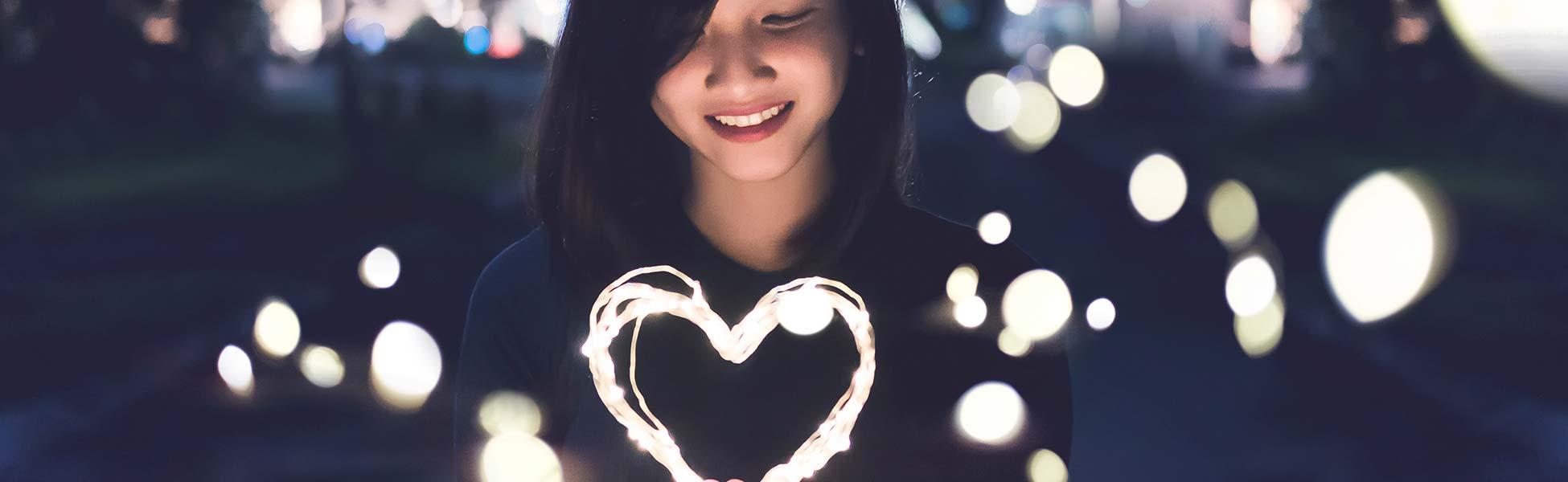 Kvinna som håller ett hjärta av lampor